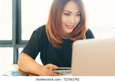 Asian stylish glasses woman designer wear black dress and red lips shopping with credit card on internet in selective focus.