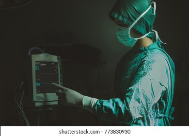 Asian Surgeon looking at medical monitor during surgery. Doctor checking monitor for patient health status.