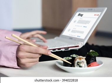 Asian Sushi Set and Woman working on Laptop Computer taking Food Roll with wooden Chopsticks