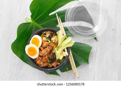 Asian take away food concept. Two poke bowl of fried rice, chicken meat, avocado and eggs in box on woocen table top view