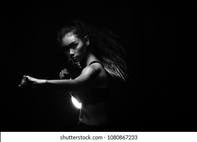 Asian Tan Skin Fitness Girl exercise boxing punch in Fog Smoke Dark background environment, studio lighting copy space b&w monotone color, concept Woman Can Do Sport, low exposure