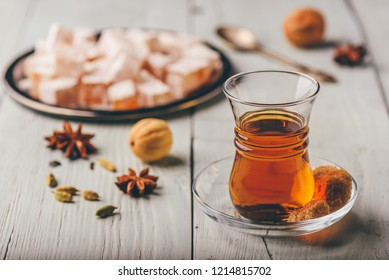 Asian tea in armudu glass with Rahat Lokum and different spices over wooden surface