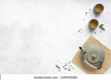 Asian Tea Set -  iron teapot and ceramic teacups with green tea and leaves. Traditional tea composition on white background, copy space.