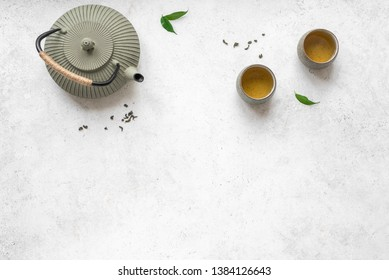 Asian Tea Set -  iron teapot and ceramic teacups with green tea and leaves. Traditional tea composition on white background, copy space, top view.