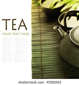 Asian tea set on bamboo mat(Green tea, palm leaf and chopsticks) with sample text