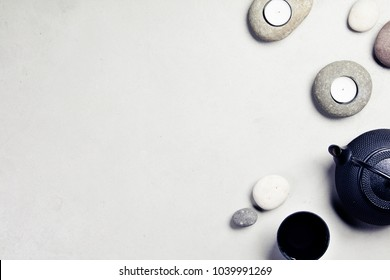 Asian tea set and spa stones on concrete background. Natural spa treatment and relaxation concept. Top view, flat lay, copyspace