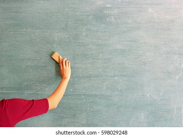 asian teacher erases on blackboard with board eraser in classroom, Education concept.