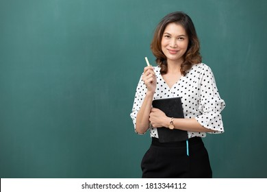 asian teacher holding chalk and book on green chalkboard background