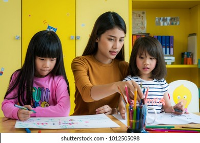 Asian teacher and preschool student in art class, this immage can use for teacher, education, school, student, kid,art, and back to school concept