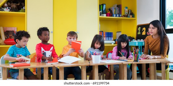 Asian teacher teach in international preschool with student form African amarican nation, Asian, and caucasian, stydy, school, kid, lerning and education concept