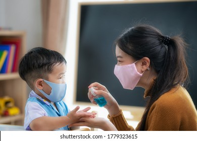 Asian teacher use bottle spray to spray alcohol liquid to hands of her student for prevent corona virus covid 19 in in her class room, in preschool.