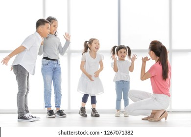 Asian teacher woman in pink shirt teach Asian girls and boy some acting to act fake cry, they stand in front of big white window.