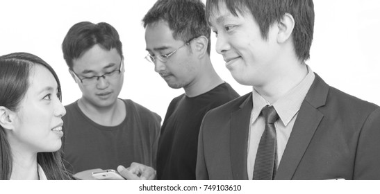 Asian teamwork standing and discussing about a project. Isolated.