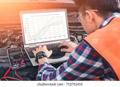 The asian technician analyze the car's engine graph on laptop computer in the garage. the concept of automotive, repairing, mechanical, vehicle and technology.