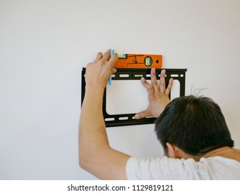 Asian technician hands holding a TV wall mount against the wall while looking for the right angle to make a mark for a drilling
