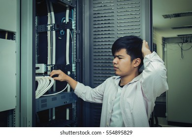 Asian Technician man checking LAN wire with confuse emotion of control room, vintage tone