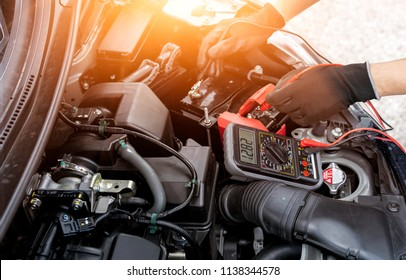 Asian technician measure voltage of battery in the car at service station, Maintenance and repair