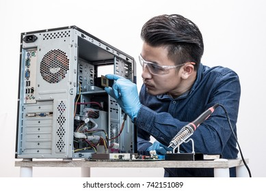 The asian technician is putting the CPU on the socket of the computer motherboard. the concept of computer hardware, repairing, upgrade and technology.