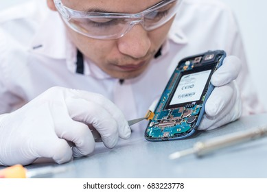 The asian technician repairing the smartphone's motherboard by soldering in the lab. the concept of computer hardware, mobile phone, electronic, repairing, upgrade and technology.