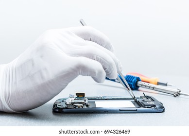 The asian technician repairing the smartphone's motherboard in the lab. the concept of computer hardware, mobile phone, electronic, repairing, upgrade and technology.