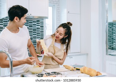 Asian teen couple are helping to make dinner. And bakery together happily. On Valentine's Day in their home.