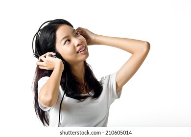 Asian teen girl listening to music with headphones.