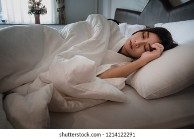 Asian teen girl lying on bed in room.Young woman sleeping on white pillow in bed
