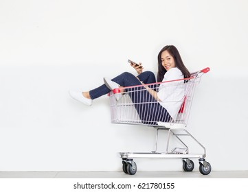 asian teen girl in shopping cart with mobile phone in shopaholic concept