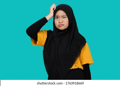 Asian Teen girl wearing headscraf/hijab holding her head feel confused with close her eye, isolated on blue background