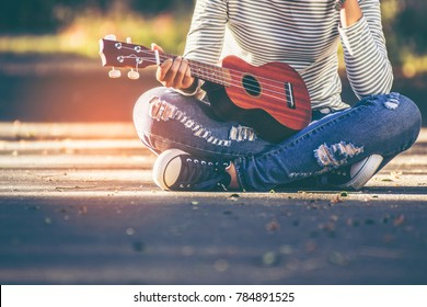 Asian teen girl wearing jeans and T-shirt playing ukulele is within the park. She was sitting on the corridor in the warm sunlight shines from the back with copy space.