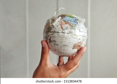 Asian teen hands hold a world covered in plastic, showing environmental problems and the effects of global warming caused by greenhouse conditions.