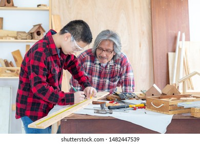 Asian teenage carpenter and his father working on woodworking table in carpentry shop. Family, carpentry, woodwork and people concept.