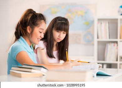 Asian teenage classmates sitting at desk and doing homework together after completion of school studies, interior of classroom on background