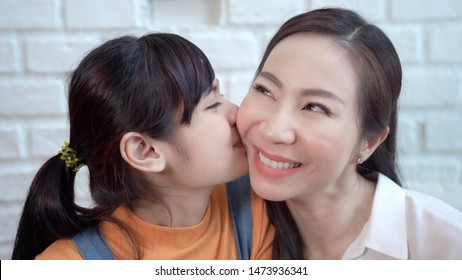 Asian teenage daughter kissing mother, showing love between mother and daughter