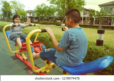 Asian teenage girl and boy playing with steel equipment for exercise at park with sun flare and space.