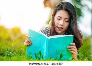 Asian teenage girl reading a book in the park on Sunday morning, a brilliant weekend. The women students are reading books, intended to prepare for university entrance exams.