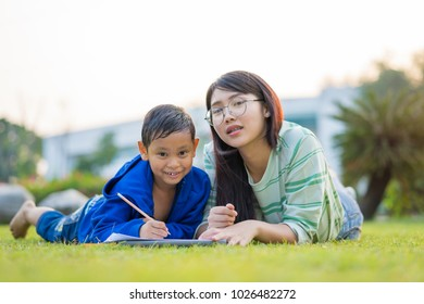 Asian teenage girl teach the boy lovingly and fun in the green meadows