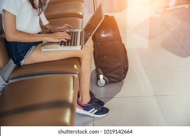 Asian teenage girl is using a laptop to check email or social network or internet at the international airport to travel on weekends.