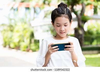 Asian teenage girl using smartphone outdoor