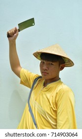 Asian teenage men wearing farmer hat and yellow shirt in his hand holding a chopper knife to chop on blue background,Acne-prone face of adolescent male,Halloween horror