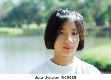 Asian teenage short hair wear white shirt in the lake