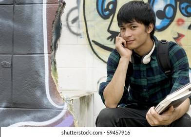 Asian teenage student holding books