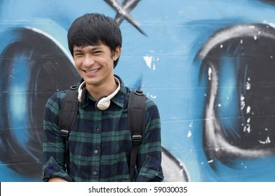 Asian teenage student wearing headphones in front of graffiti wall