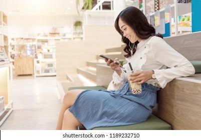 asian teenage urban behavior like shopping drink coffee siting in sharing working space at modern trade center. Enjoy digital mobile phone.