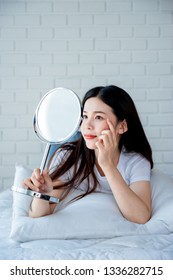 Asian teenage woman  looking at mirror and squeeze acne problem on her face, skin care concept.