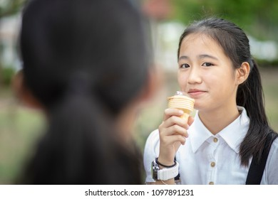 asian teenager eating icecream cone with happiness face