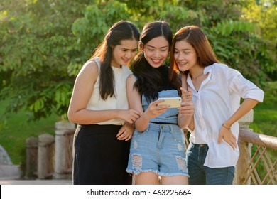 Asian teenager friends outdoors in park using mobile phone
