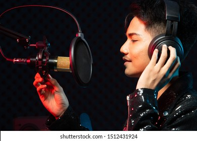 Asian Teenager man black hair earmuff headphone sing a song loudly power sound over hanging microphone condenser, speakers, composer note book and monitor. Studio Sound Proof Absorbing wall room