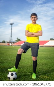 Asian teenager on a football field with a ball, sports and entertainment