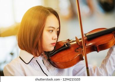 Asian teenager playing violin.